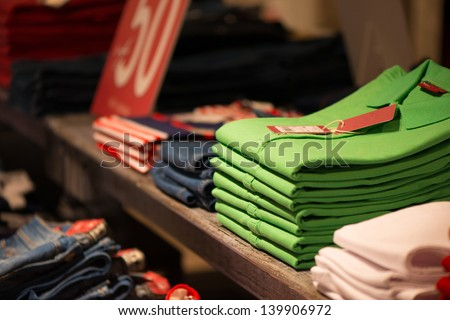 Various color shirts at shelf in shop