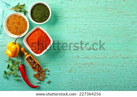 Various colorful dry and fresh spices on blue wooden background - stock photo