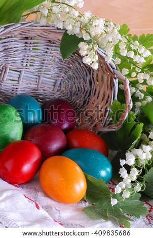 various colorful easter eggs and punnet  with may-lily flower - stock photo