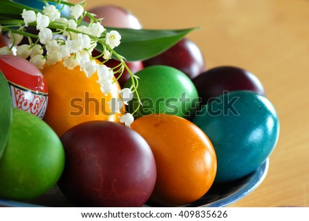 various colorful easter eggs on plate with may-lily flower - stock photo