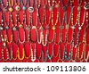 Various colorful Necklaces on red background at flea market in India - stock photo
