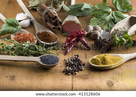 Various colorful spices and food drugs on wooden table, some are dried and ground, others are fresh