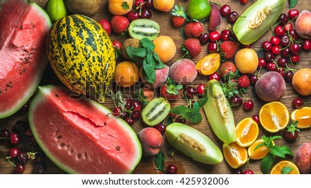 Various colorful tropical fruit selection on rustiv wooden background, top view. Watermelon, melon, strawberries, cherries, kiwi, peaches, apricots, oranges, limes. Horizontal - stock photo