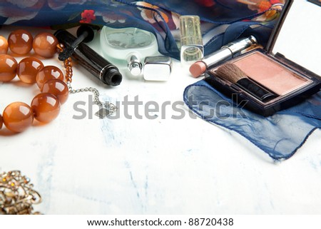 Various cosmetics and beads on white wooden table - stock photo