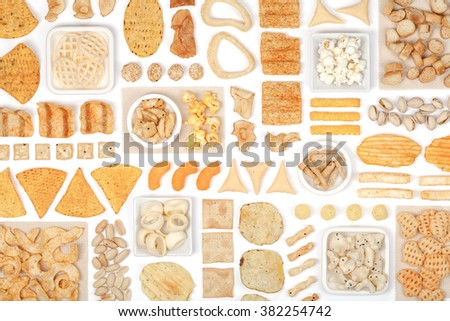 various crisps and snacks on white background top view - stock photo