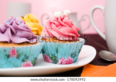 various cupcakes on a plate on pink background  - stock photo