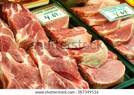 Various cuts of pork chops and portions on display at a meat market