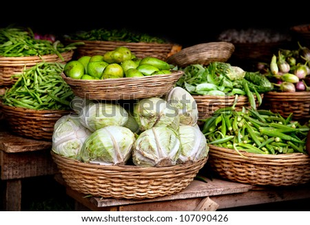 Various different vegetables and mango in wooden baskets at the market, Kumly, Kerala, India - stock photo