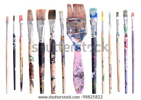Various dirty paint brushes displayed side by side - stock photo