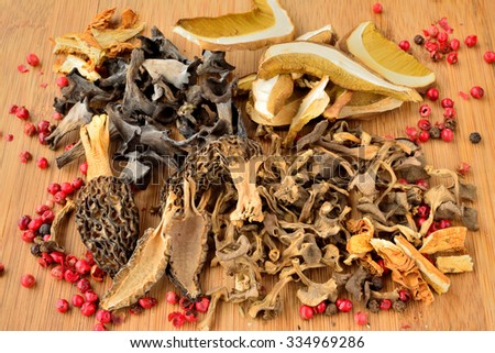 Various dried mushrooms, Penny Bun or Cep, Morels, Horn of Plenty mushrooms, Golden Bootleg mushrooms and Trumpet Chanterelle mushrooms, left on wooden chopping board with some red pepper - stock photo