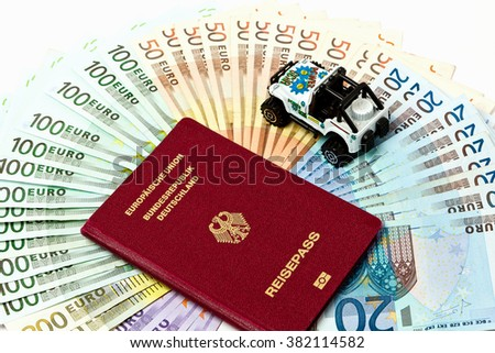 Various euro bills 500 200 100 50 Euro banknotes lying on a table. On top of the money lies a passport as a symbol for a journey - stock photo