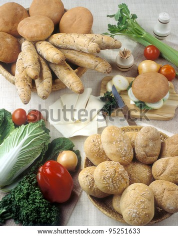 Various European bakery goods with fresh vegetable around it - stock photo