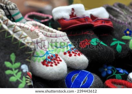 Various felt slippers on the market counter - stock photo
