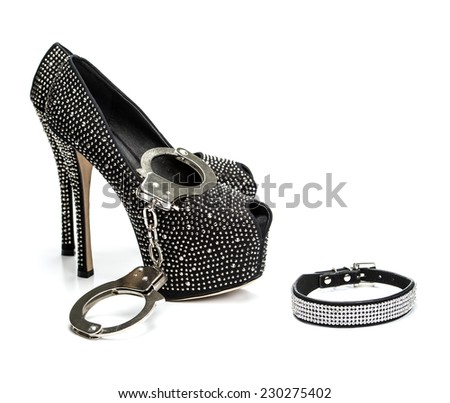 Various fetish stuff for role playing and BDSM: hand cuffs, leather collar and shiny high heels shoes with rhinestones - stock photo