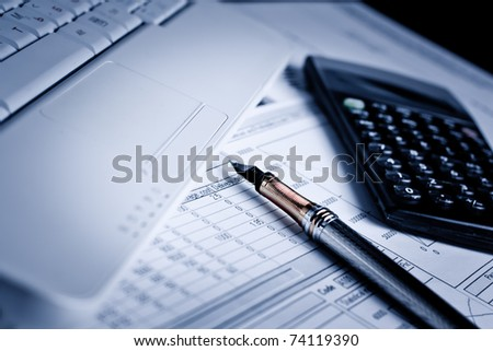 Various financial charts on the table with laptop, calculator and pen - stock photo