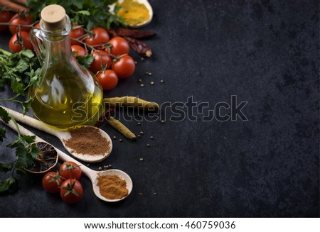 Various food ingredients and spices on rustic black background with copyspace.