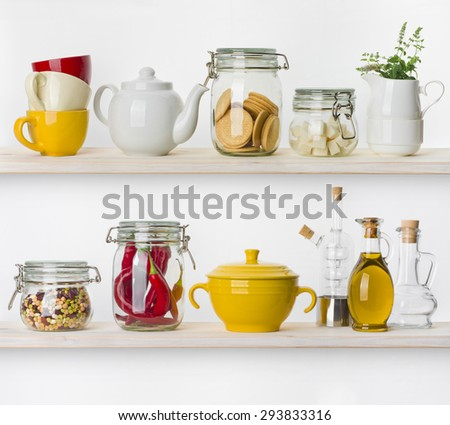 Various food ingredients and utensils on kitchen shelves isolated - stock photo