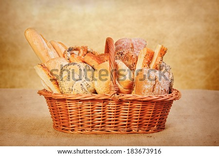 Various fresh bakery products in wicker basket - stock photo