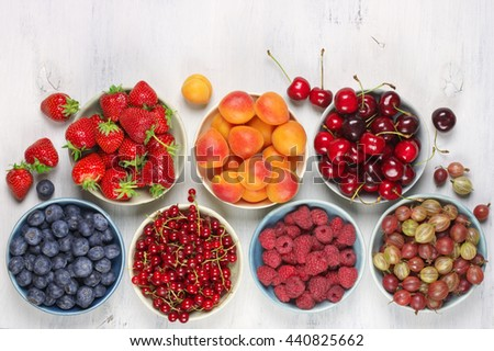 Various fresh fruits in bowls in rows on white wooden background: strawberries, blueberries, raspberries, cherries, red currants, gooseberries and apricots. Top view.
