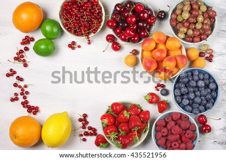 Various fresh fruits in bowls on white wooden background with copy space: strawberries, blueberries, raspberries, cherries, red currants, gooseberries, apricots, orange, lemon and limes. Top view.