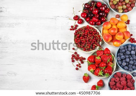 Various fresh fruits in bowls on white wooden background with copy space: strawberries, blueberries, raspberries, cherries, red currants, gooseberries and apricots. Top view.