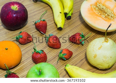 Various fresh fruits spread on wooden table in the kitchen. - stock photo