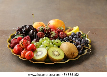various fresh organic berries on a vintage silver plate - stock photo