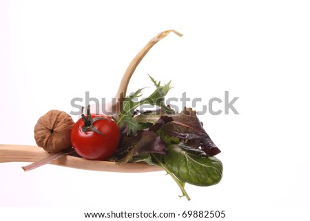 Various fresh products on a wooden spoon to make a healthy salad - stock photo