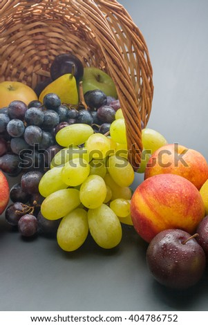 Various fresh ripe fruits close up: plums, peaches, pears, apples and grapes scattered from a wicker basket on neutral  background - stock photo