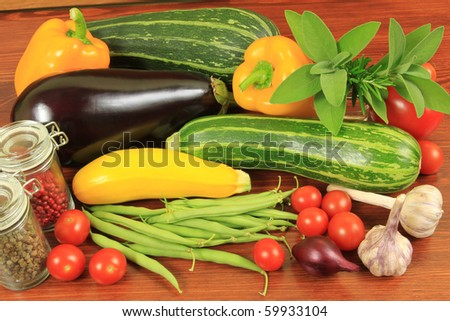 Various fresh vegetables on a wooden table: tomatoes, beans, courgettes, aubergine, garlic, onion and chanterelles.