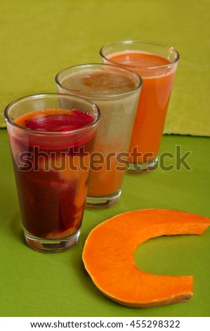 Various freshly squeezed vegetable juices with the hunk of pumpkin  on green background.  - stock photo