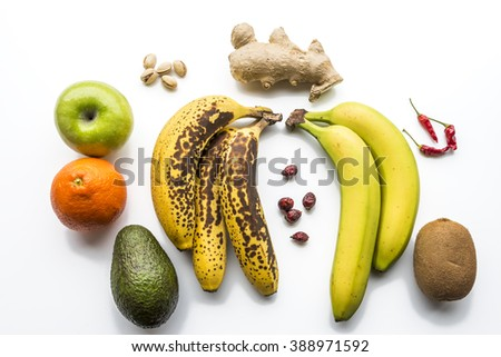 Various fruits flat layed on white background. Bananas, apple, kiwi, pistachio, hip, chilly pepper, orange and ginger. Healthy fruits. - stock photo
