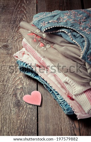 Various girls clothes on an old wooden table and a small pink wooden heart - stock photo