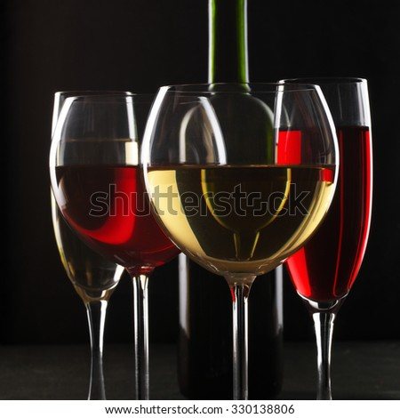 Various glasses of red and white wine with abstract pattern and bottle on black background.