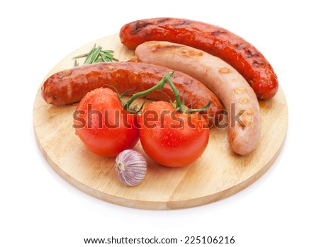 Various grilled sausages with condiments and tomatoes on cutting board. Isolated on white background - stock photo