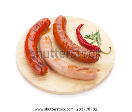 Various grilled sausages with spices on cutting board. Isolated on white background - stock photo