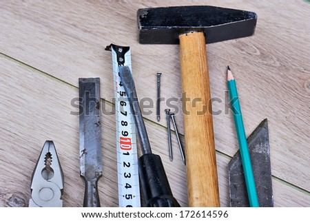 Various hand tools sitting on a wooden deck. - stock photo
