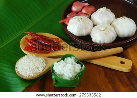 Various ingredients for cooking thai food including red onion, garlic, dry chili, jasmine rice and cooked rice. This is thai traditional lifestyle. - stock photo