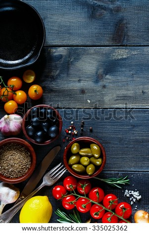 Various ingredients, herbs and spices for cooking (tomatoe, garlic, pepper, rosemary, olives,lemon) on dark wooden background with space for text. Top view. Vegetarian food, health or cooking concept. - stock photo