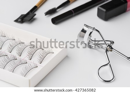 Various instruments women use for make-up. Typical set of every fashionable lady. Curler, special brushes, mascara and false eyelashes are popular all round the year. - stock photo