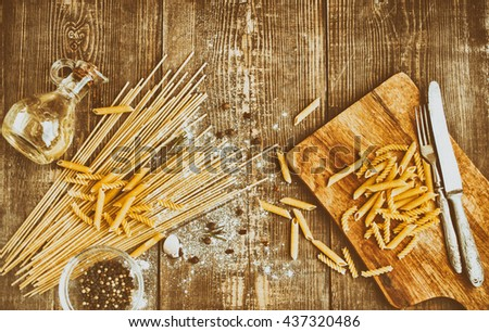 Various italian pasta and spices on the wooden background.  Food composition on a wooden table. Italian spaghetti. Retro and vintage tone. Mediterranean kitchen. Top view