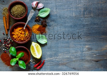 Various kind of spices and herbs over dark old wood. Food and cuisine ingredients. Background with space for text. - stock photo