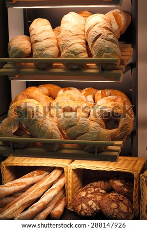 Various kinds of fresh baked bread on the shelves at the bakery. Shallow focus. - stock photo