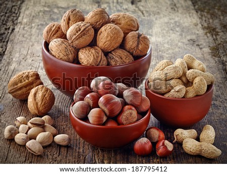 various kinds of nuts on old wooden table - stock photo