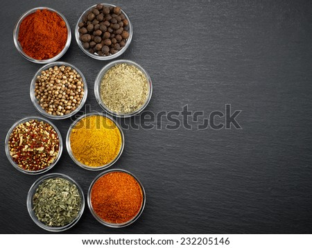 various kinds of spices on black stone surface - stock photo