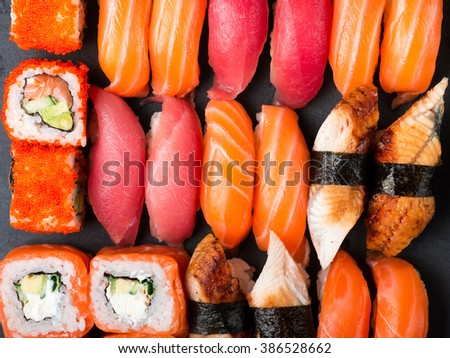 Various kinds of sushi served on black stone. Sushi Set sashimi and sushi rolls, close-up top view - stock photo