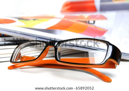 Various magazines with orange colored glasses over white background - stock photo
