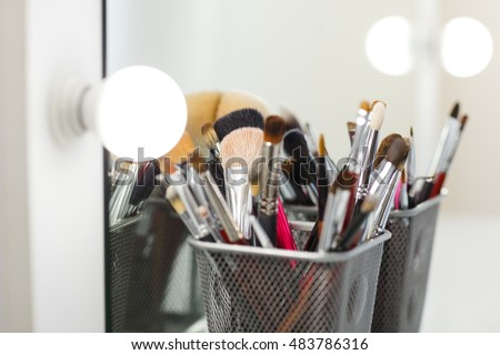 Various makeup brushes on light background