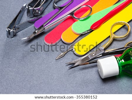 Various manicure tools on gray textured surface. Nail clippers, nail and cuticle scissors, colored nail files, double ended cuticle trimmer / pusher, cuticle remover, nail art brushes and nail oil - stock photo