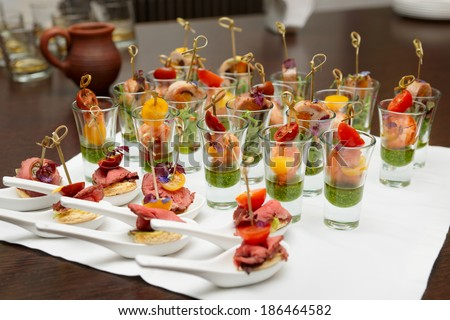 Various Meat And Seafood Snacks In Shot Glasses On Table